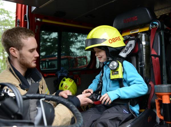 Victor Voie Opland (7 år) fikk en drømmedag på Sognsvann med blant annet besøk inne i en av brannbilene, hvor han fikk kyndig hjelp fra brannmann Bjørn Larsen.